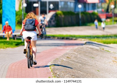 Woman riding a bicycle. Nida resort near Klaipeda in Neringa at the Curonian Spit in the Baltic Sea in Lithuania.