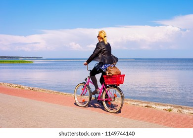 Woman riding a bicycle. Nida resort near Klaipeda in Neringa in the Curonian Spit in the Baltic Sea in Lithuania.