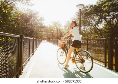 Woman riding bicycle on a bike path marked with symbol.