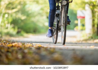 Woman riding a bicycle outdoors on a path in the park in Autumn.