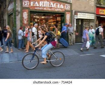 Woman riding a bicycle past a pharmacy in Barcelona, Spain