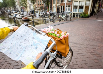 Woman riding a bicycle with tourist map on the street in Amsterdam city. View on the hands holding map