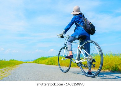 Woman riding a bicycle while watching the blue sky