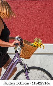 woman riding bike with basket with red wall in background