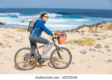 Woman riding bike on a beach by the water