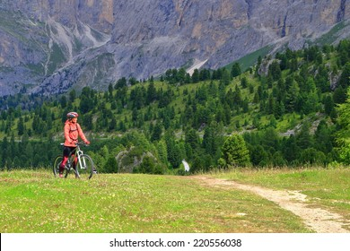 Woman riding a bike on the mountain road near Sella pass, Dolomites Alps, Italy