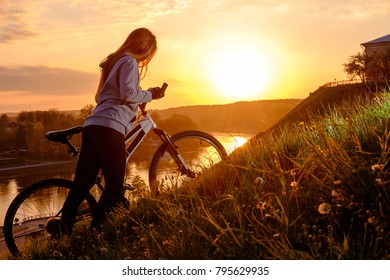 woman riding bike over hills in sunset