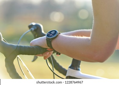 Woman riding a bike and using smartwatch to heart rate monitor