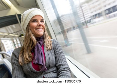 Woman riding in a bus and looking happy