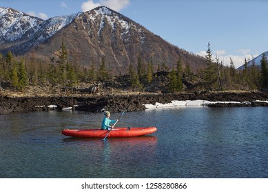 Woman is riding canoe on lake in mountain area in spring time