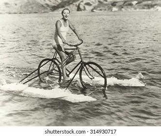 Woman riding cycle boat on lake