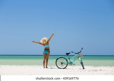Woman riding her bike along the beach in a sunny day