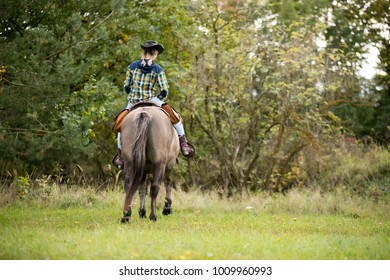 Woman riding a horse during sunset at countryside