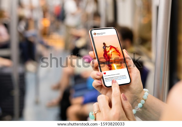 Woman riding in metro and viewing someone's photo on mobile phone.