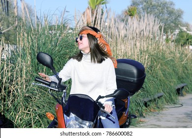 The woman riding the motorcycle. She has a bandana and sunglasses.