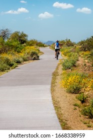 Woman riding mountain bike down a paved path in the McDowell Mountain Regional Park in Scottsdale Arizona, USA on spring day