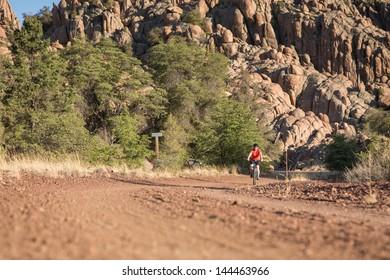 Woman Riding a Mountain Bike in Rocky Landscape.