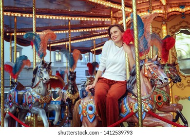 Woman riding on a traditional vintage carousel in a city park