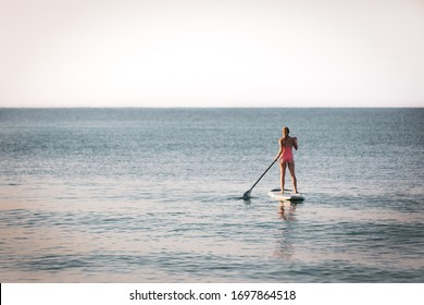 woman riding paddle board on calm water