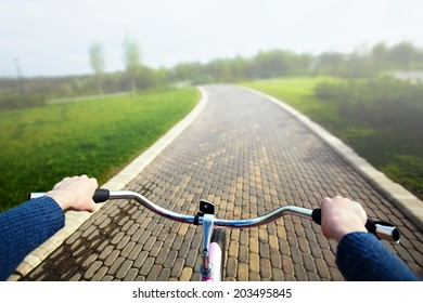 Woman riding pink bicycle in park, handlebar view.