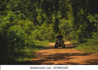 woman riding quad atv running on wilderness field