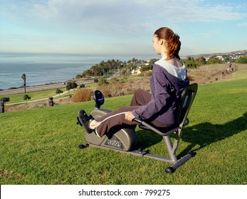 Woman riding / spinning on recumbent bike at sea Cliff!