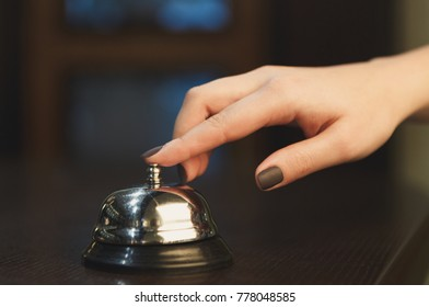 Woman ringing hotel service bell to attract attention in modern hotel, dark background, copy space