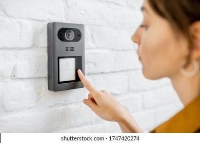 Die Frau klingelt mit einer Kamera auf der weißen Ziegelwand auf der Wohngegend