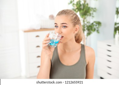 Woman rinsing mouth with mouthwash in bathroom. Teeth care