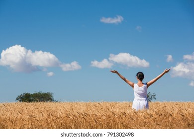 woman in a ripe golden wheat field hugging nature, blue sky with clouds, sunny day