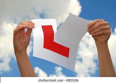 Woman ripping a car L plate held towards the sky after succeeding in passing driving test