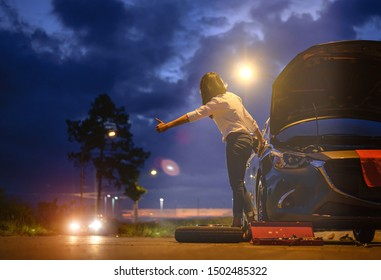 Woman rise hand calls for help and assistant at dark of the night, scary and worry alone in the dark, car engine failure or tire need replacement