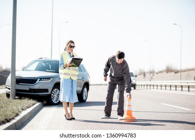 Woman and road assistance worker during the road accident on the highway