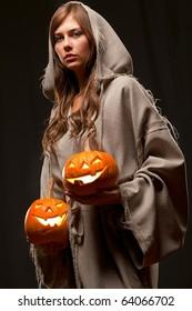 woman in robe holding halloween pumpkins