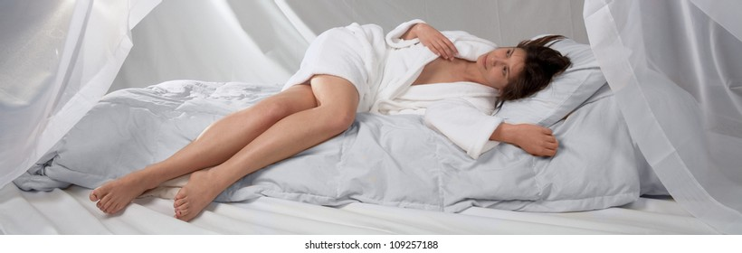 Woman in Robe Lying on Bed