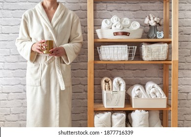 Woman in robe is standing and holding white wire basket of folded bed sheets near organized linen closet in bathroom. Sorted and folded towels in white wicker and wire baskets placed on wooden shelves