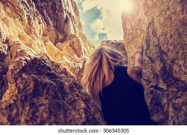 woman rock climbing up through narrow mountainous boulders with shallow depth of field with view of sky with high contrast and instagram filter