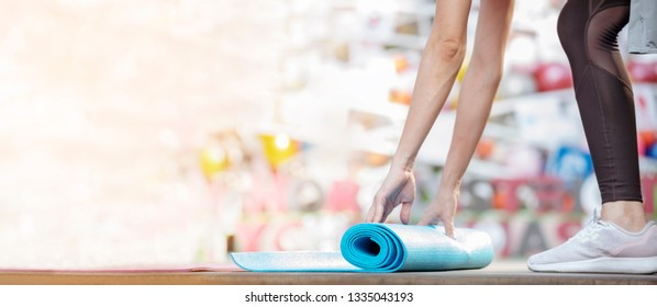 Woman roll yoga mat fitness workout people close up on hands when rolling mat. Healthy woman practice meditating concentration. Banner with copy space. Healthy fitness woman lifestyle concept.