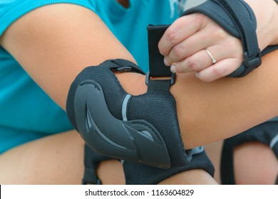 Woman rollerskater putting on elbow protector pads on her hand and wearing wrist guards