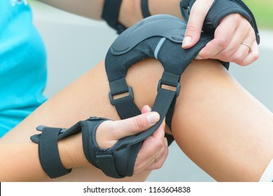 Woman rollerskater putting on knee protector pads on her leg and wearing wrist guards