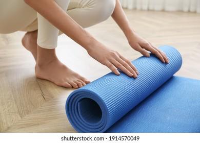 Woman rolling blue yoga mat indoors, closeup