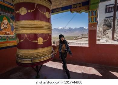 Woman rolling Buddhist prayer wheels in Ladakh, India