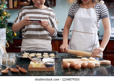 Woman rolling out dough whne her daughtr photograping raw cookies on tray