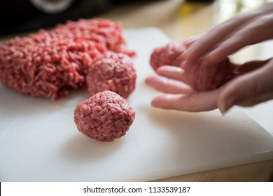 Woman rolling raw mixed minced meat, half beef, half pork, for burger patty's