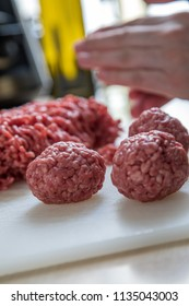 Woman rolling raw mixed minced meat meatballs, half beef, half pork, for burger patty's