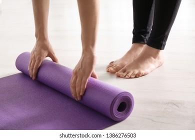 Woman rolling yoga mat on floor indoors, closeup