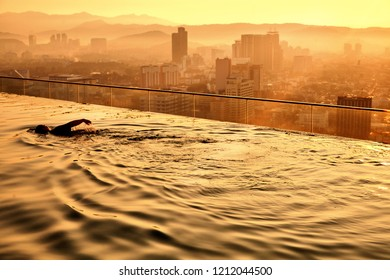 woman at the rooftop swimming enjoying the golden morning sun rise