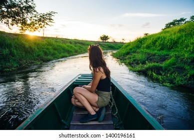 Woman rowing oars in the boat. The view from the back.