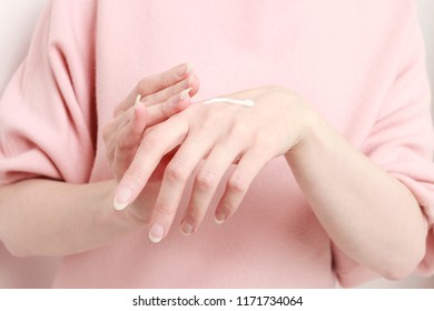 Woman rubbing cream in her hands. Daily skin care.