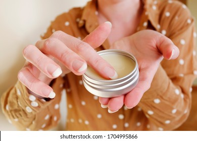 Woman is rubbing cream in her hands.